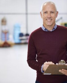 Portrait of a factory manager standing with a clipboard
